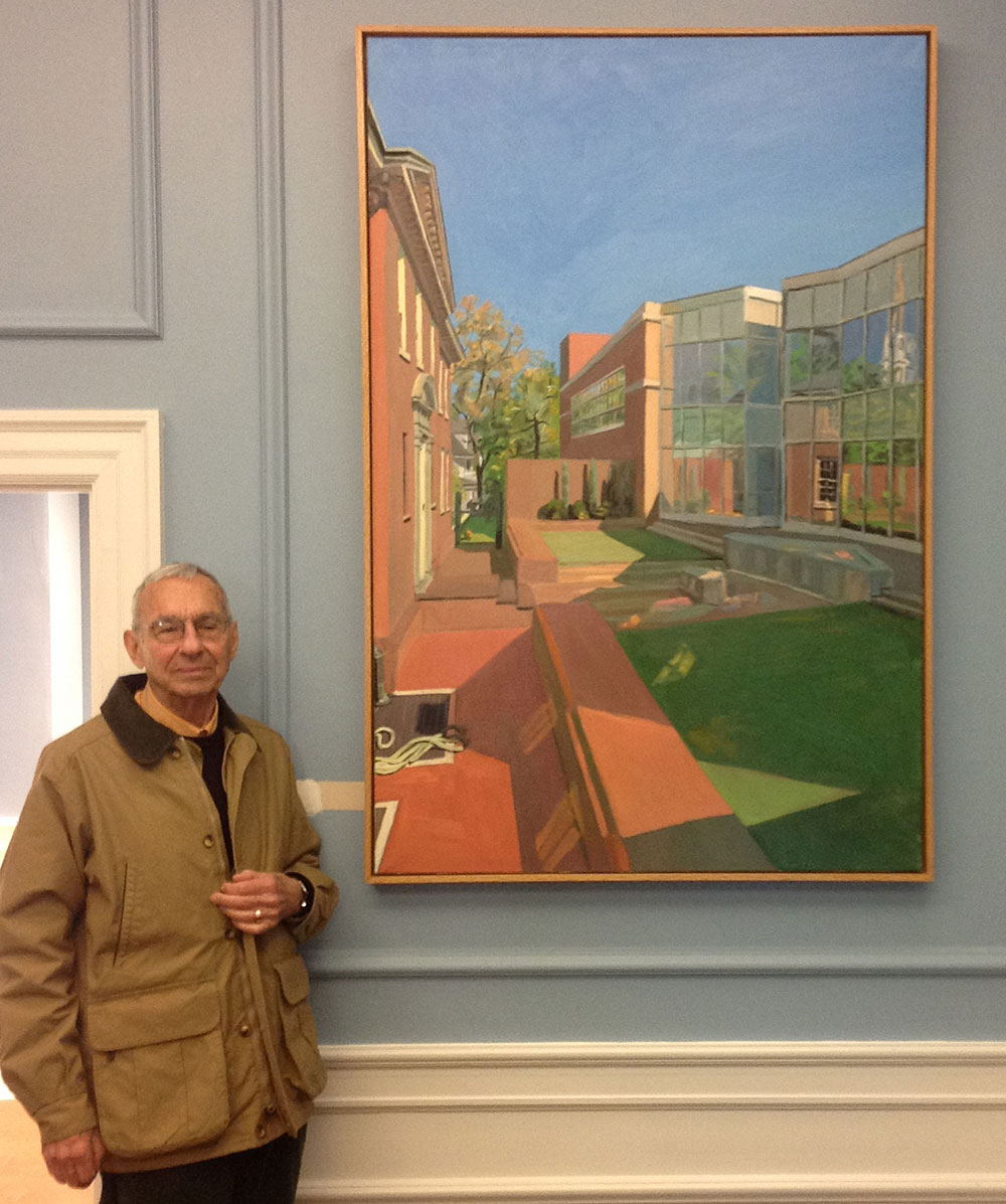 A man stands in front of a painting of the Ackland Art Museum courtyard