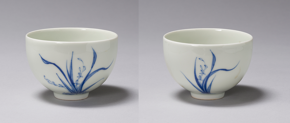 front and back view of a porcelain tea cup with blue leaves painted on it