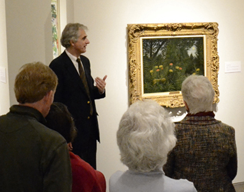 A curator stands beside a painting, talking to museum visitors
