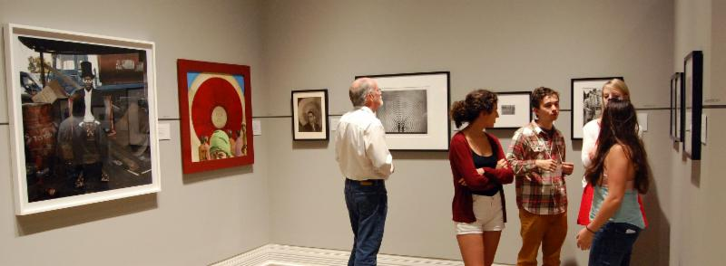 Museum visitors look at works of art on a gallery wall