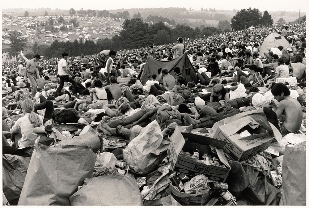 black and white photo of many people laying in the grass at Woodstock