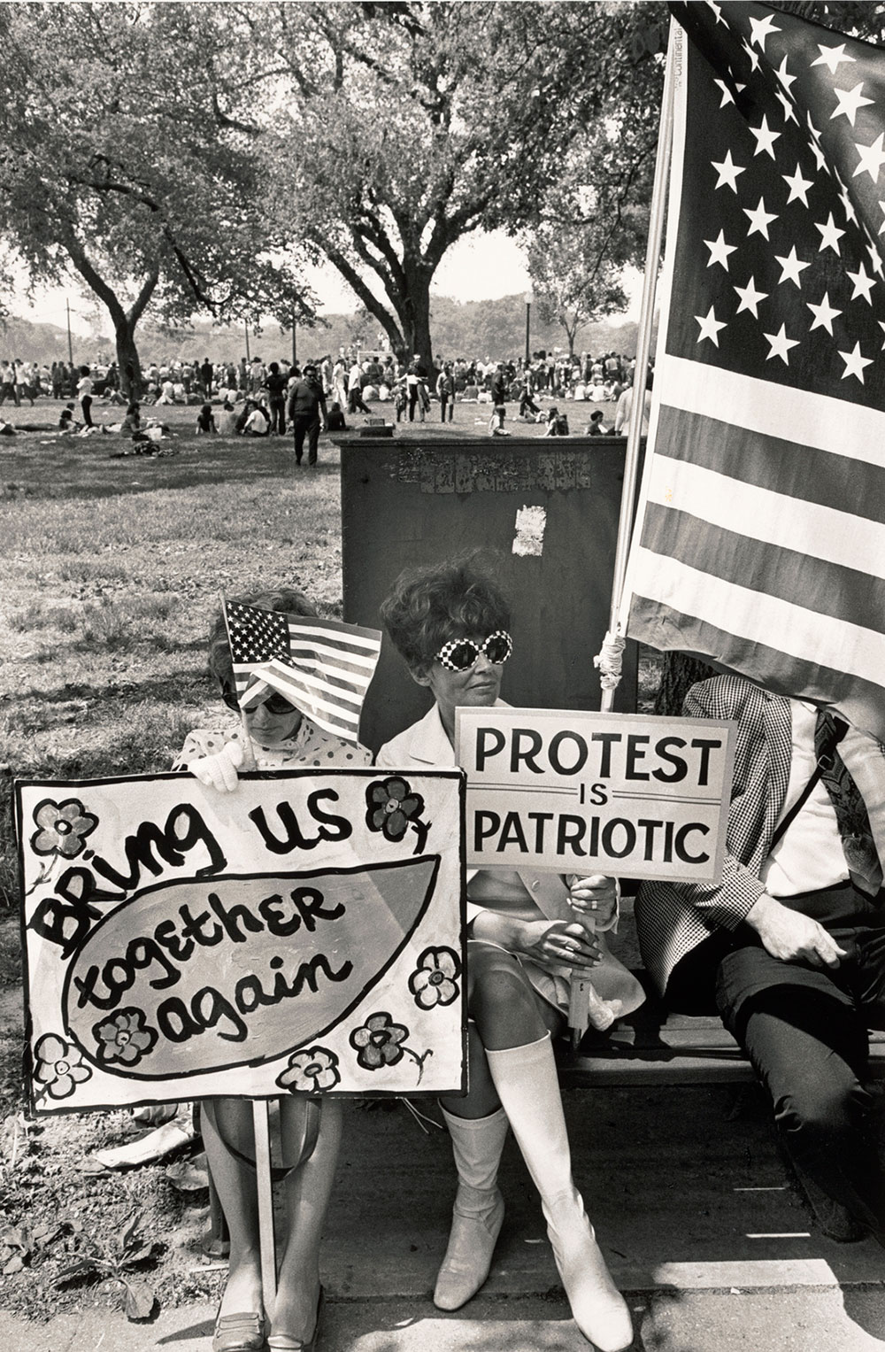 black and white photo of a woman sitting with protest signs and an American Flag