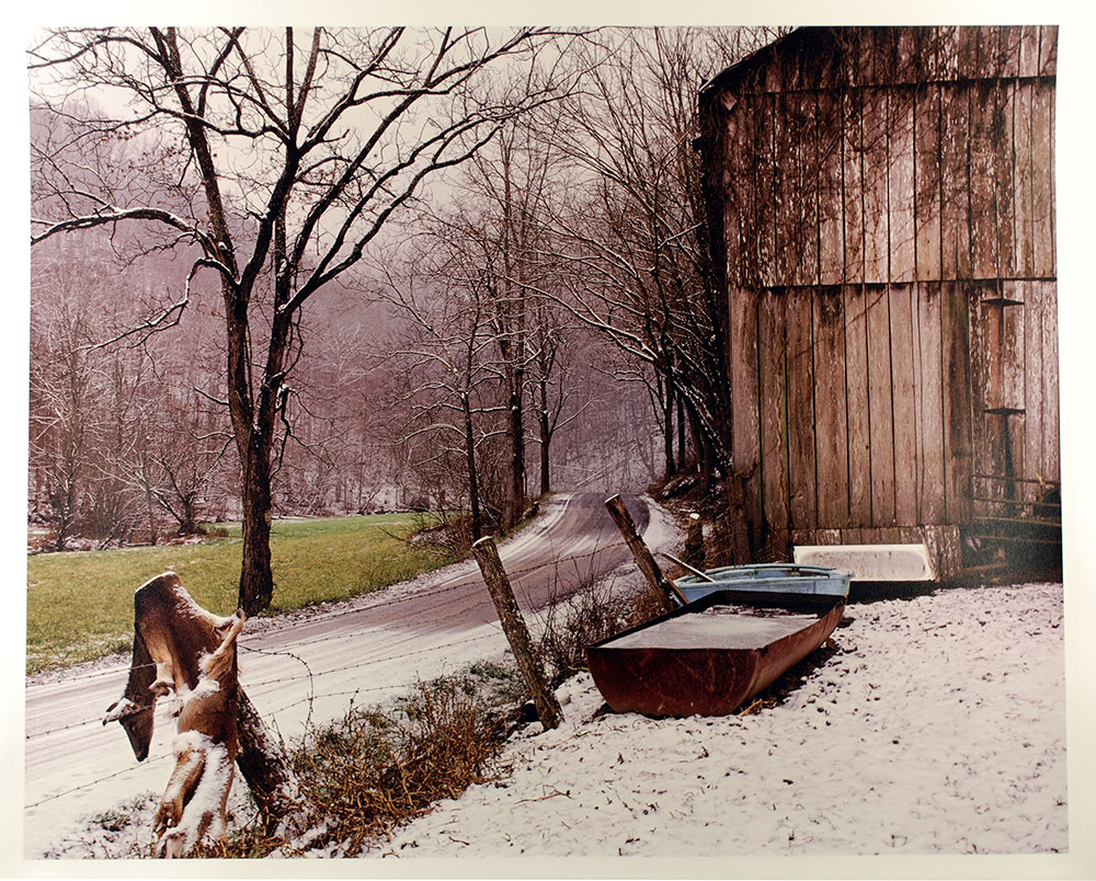 landscape photo with a barn, trees, and a deer skin