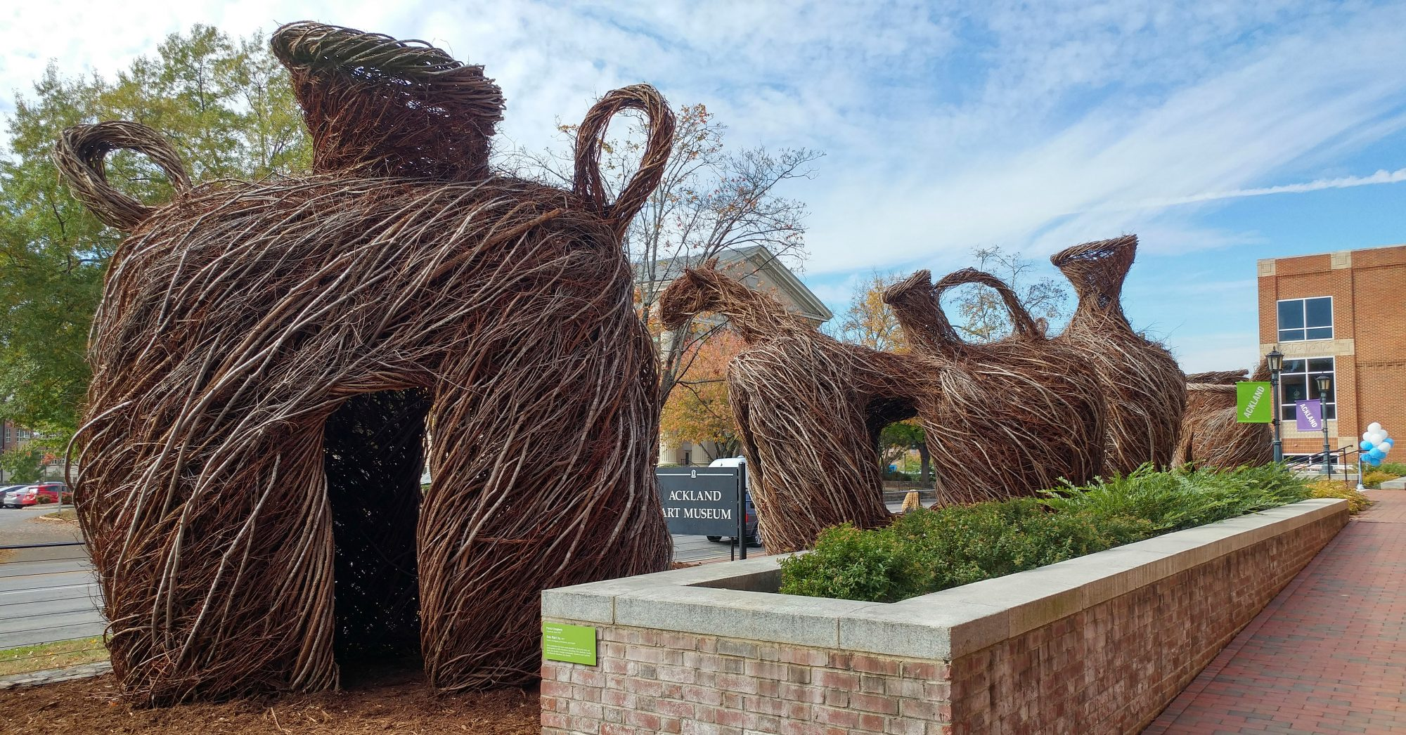 A row of giant vessel-shaped sculptures made out of sticks