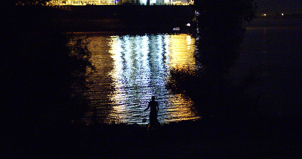 Person standing by river at night