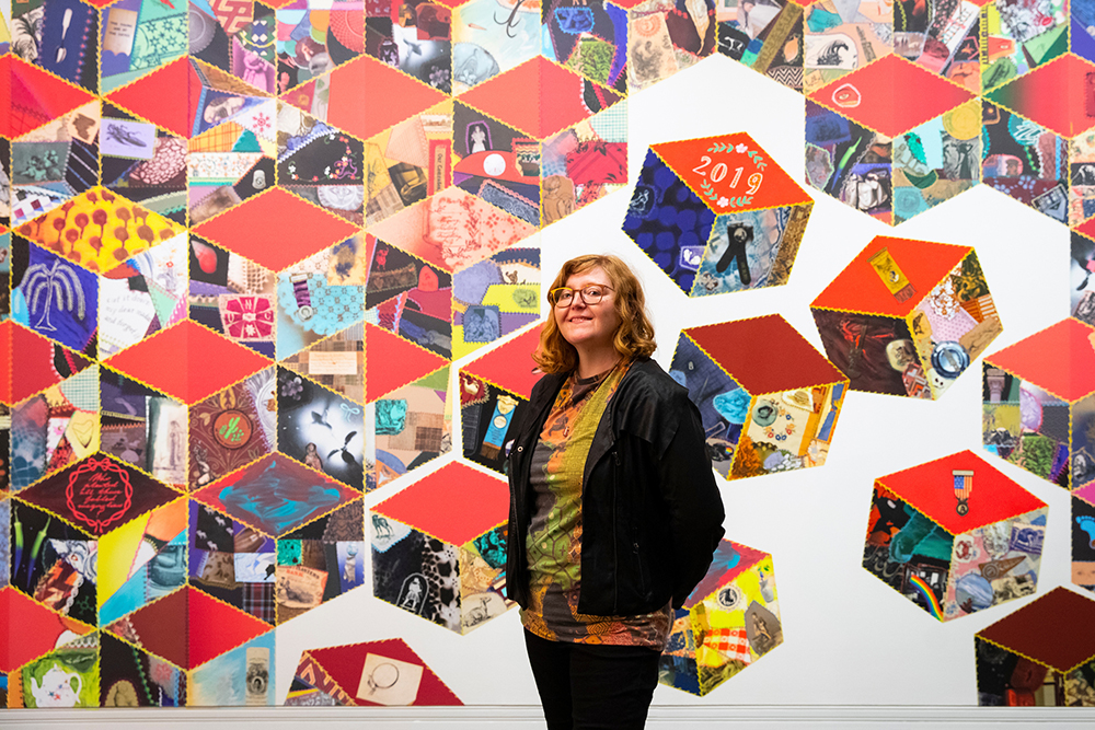 Artist in front of wall-sized art installation