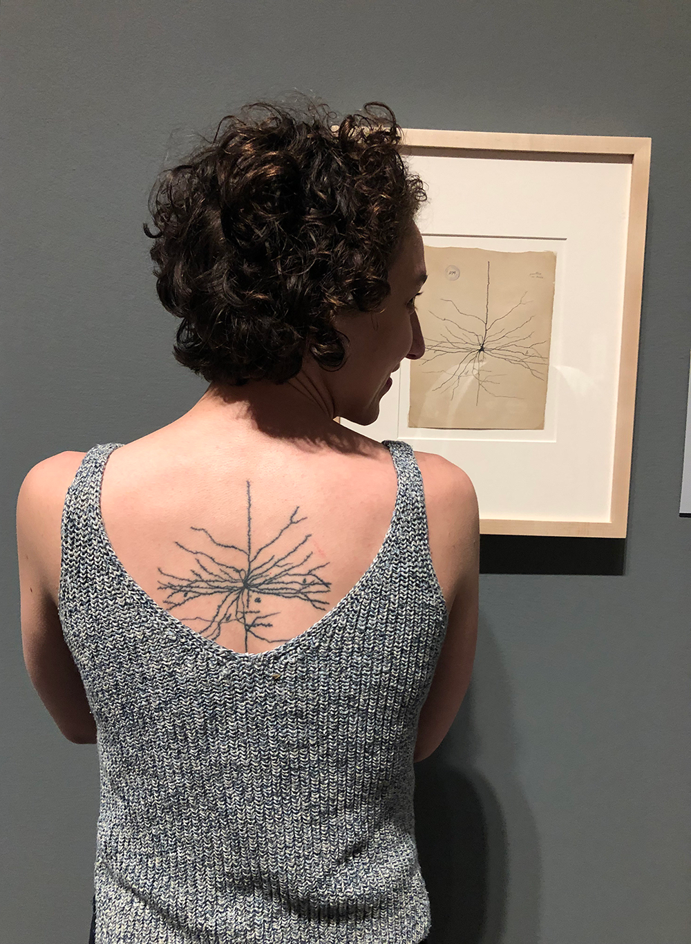 Photo of a woman from behind showing the pyramidal neuron tattoo on her back while standing in front of a drawing of a pyramidal neuron