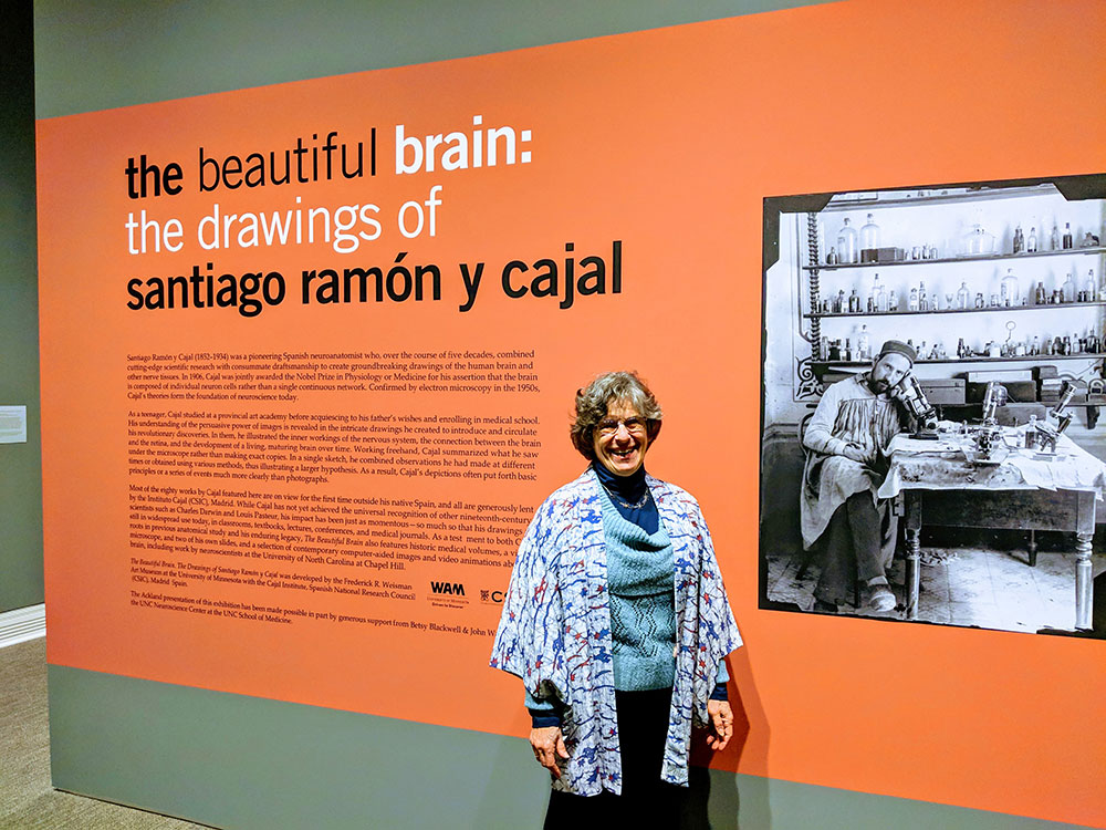 A woman stands in front of a museum wall with text about the beautiful brain exhibition