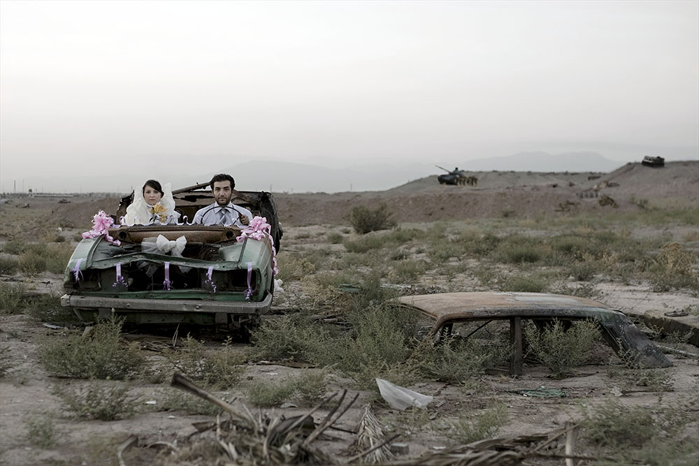 Wedding couple in car in burned out landscape