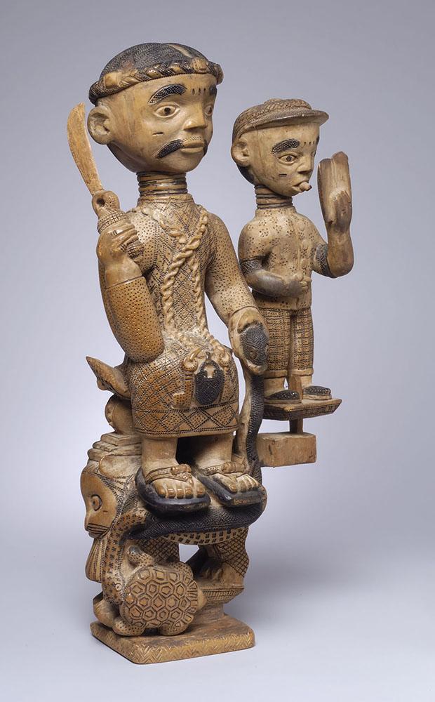 Wooden sculpture of large figure holding smaller figure