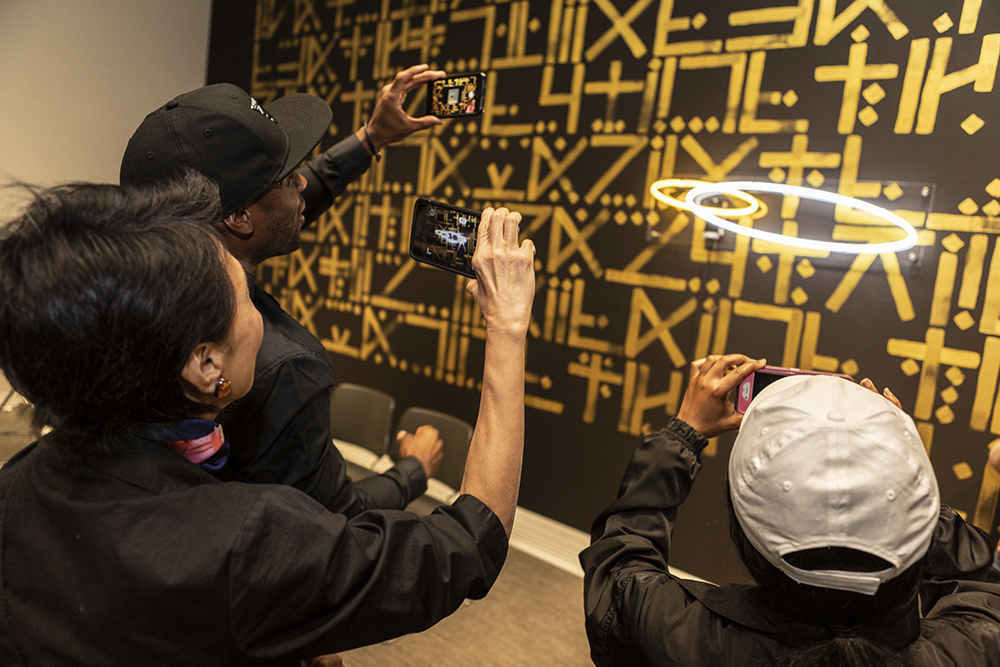 Three people use a cellphone app to unlock a secret message in a painting