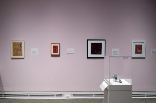 A pink wall in a museum gallery shows four paintings. There is a display case in the foreground showing a small sculpture of a show.