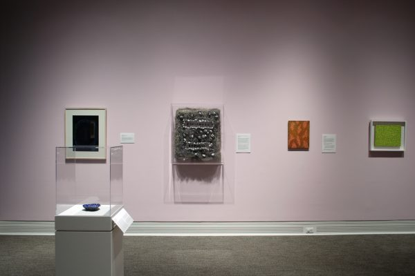 A pink wall in a museum gallery shows three paintings and one mixed media sculpture. There is a display case in the foreground showing a small ceramic sculpture.