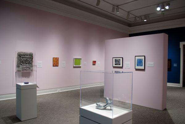 A museum galley with pink and blue walls showing a variety of paintings and sculptures. In the foreground are two display cases with sculptures inside.