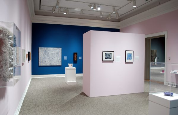 A museum galley with pink and blue walls showing a variety of paintings and sculptures