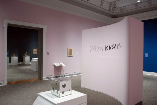 a museum gallery with a freestanding pink wall that says Yayoi Kusama: Open the Shape Called Love. A mirror box in a display case is in the foreground. To the left, a doorway leads into a different gallery.