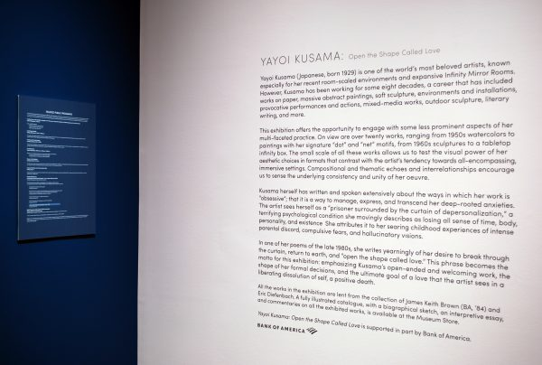 """the intersection of two museum gallery walls painted pink and blue with vinyl exhibition text about the Yayoi Kusama exhibit """"Open the Shape Called Love"""""""