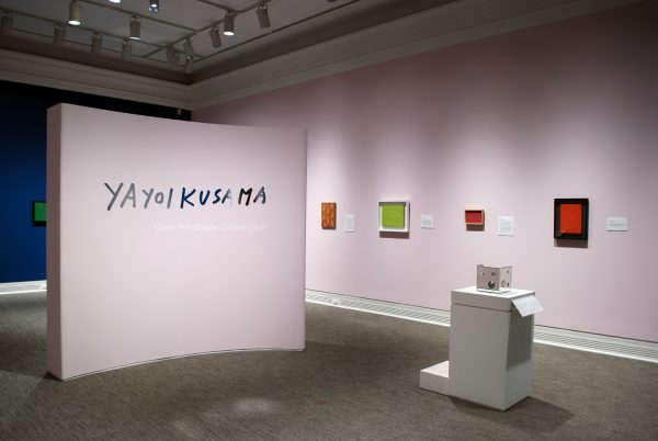 a museum gallery showing four paintings on a pink wall and one mirror box in display case. A freestanding pink wall has the words Yayoi Kusama: Open the Shape Called Love.