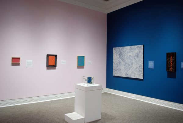 a museum gallery showing three paintings on a pink wall, one painting and one sculpture on a blue wall, and one mirror box in a display case