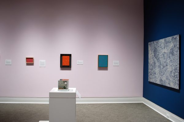 a museum gallery showing three paintings on a pink wall, one painting on a blue wall, and one mirror box in a display case