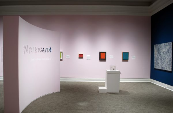 a museum gallery showing four paintings on a pink wall, one painting on a blue wall, and one mirror box in display case. A freestanding pink wall has the words Yayoi Kusama: Open the Shape Called Love.