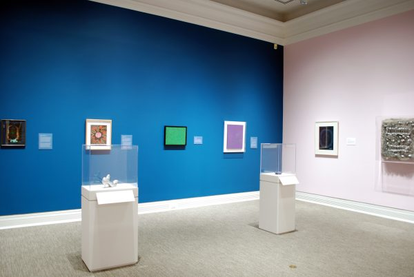 a museum gallery showing one painting and one sculpture on a pink wall, four paintings on a blue wall, and two sculptures in display cases
