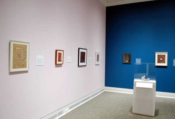 a museum gallery showing four paintings on a pink wall, two paintings on a blue wall, and one sculpture of a shoe in a display case