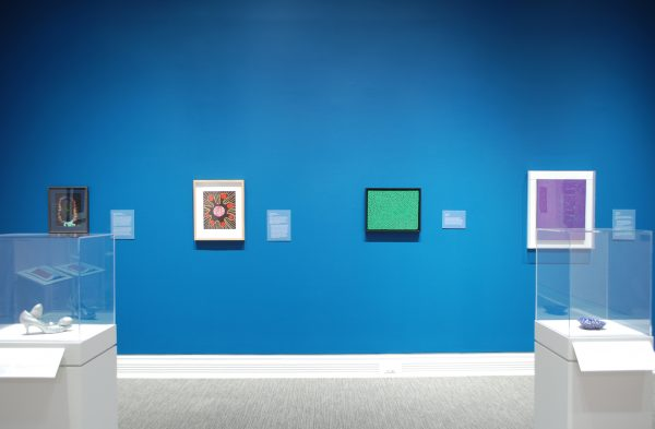 A blue wall in a museum gallery shows four paintings. There are two display cases in the foreground showing small sculptures.