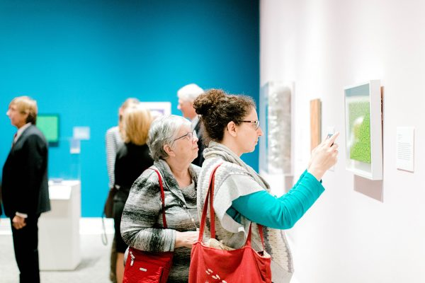 a museum gallery with a group of people in the background and two women in the foreground looking at a green painting. One of the women takes a picture of the painting on her phone.