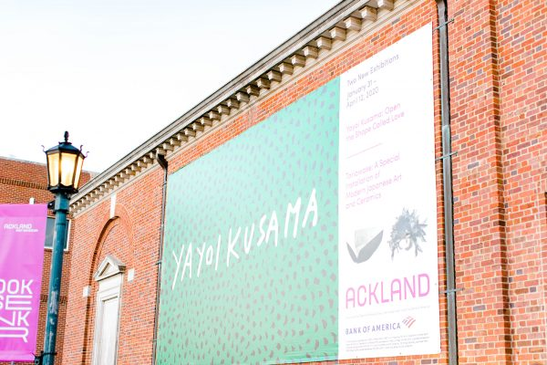 the exterior of the Ackland Art Museum building with a banner advertising the Yayoi Kusama exhibition