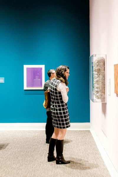 a woman from the side looking at a silver sculpture on a gallery wall. A man behind her looks at another painting. In the background, a purple painting hangs on a blue wall.