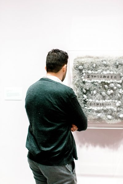 a man from behind looking at a silver mixed media sculpture hanging on a gallery wall