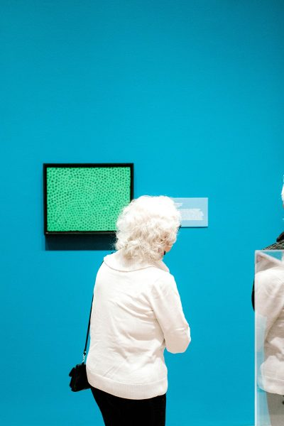 a woman from behind looking at a green painting on a blue gallery wall