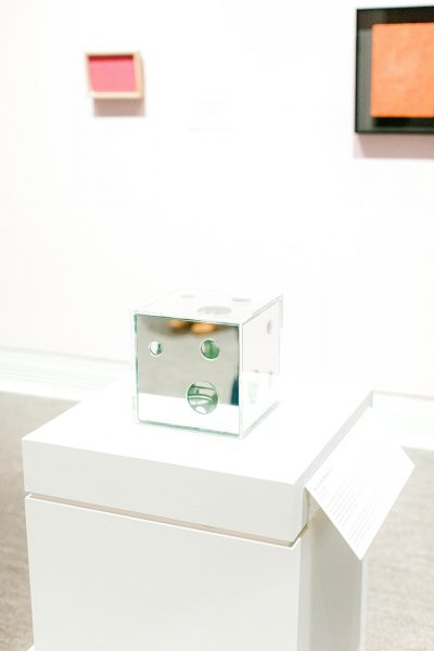 a mirror box in a display case, installed in front of a gallery wall showing two paintings in the exhibit Yayoi Kusama: Open the Shape Called love