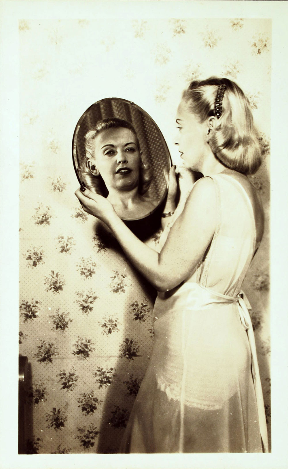 photo of a woman wearing a nightgown and looking at herself in a mirror