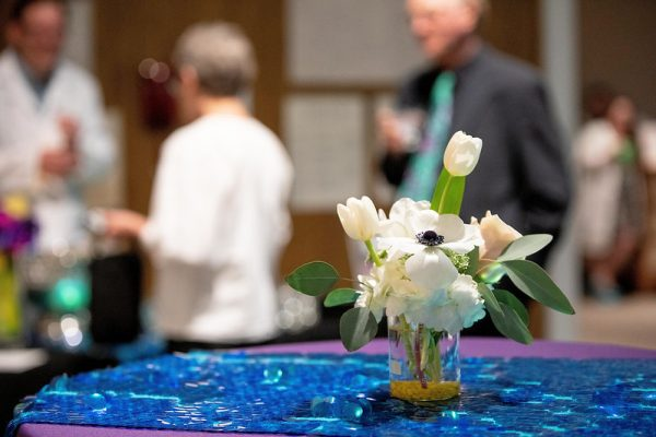 A flower arrangement on a table in the Ackland's Art& space with event guests in the background