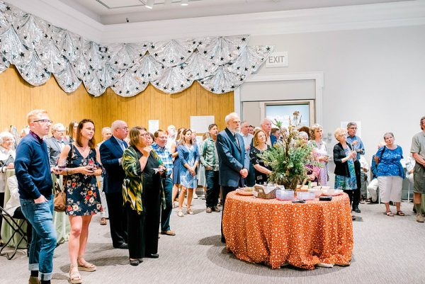 Event attendees at a cocktail party gather to listen to a speaker in the Ackland's Art& event space