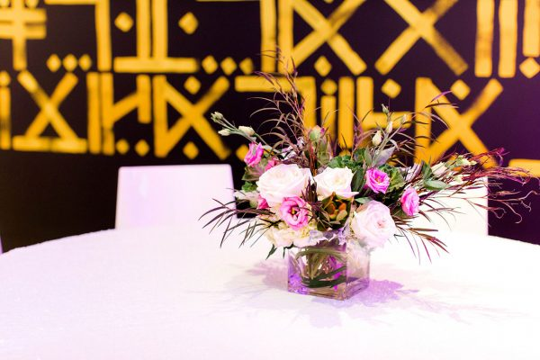 A flower arrangement for an event on a table in the Ackland's Art& space