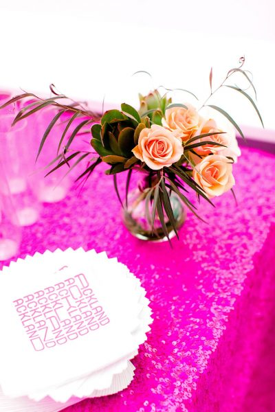 A serving table with a sequined tablecloth, flowers, and champagne glasses for a museum fundraising event