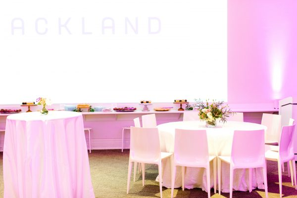 A formal table setting, food service, and audio-visual display in the Ackland's Art& space during a museum event