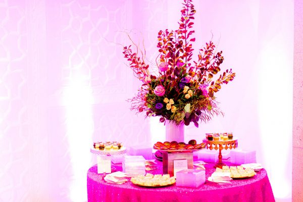 A dessert table with a large floral arrangement, sequined linens, and colored up-lighting in the Ackland lobby for an event in downtown Chapel Hill