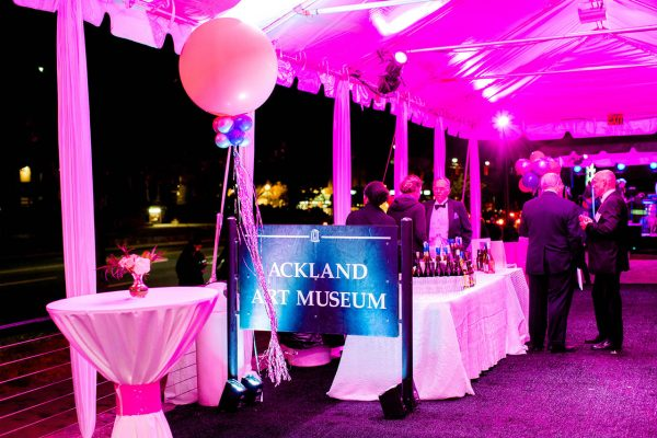 The inside of an event tent set up with formal tables and balloons on the Ackland terrace - one of its outdoor event spaces