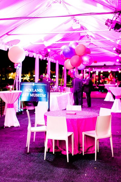 Another view of an outdoor event space - The inside of a tent set up with formal tables and balloons on the Ackland terrace