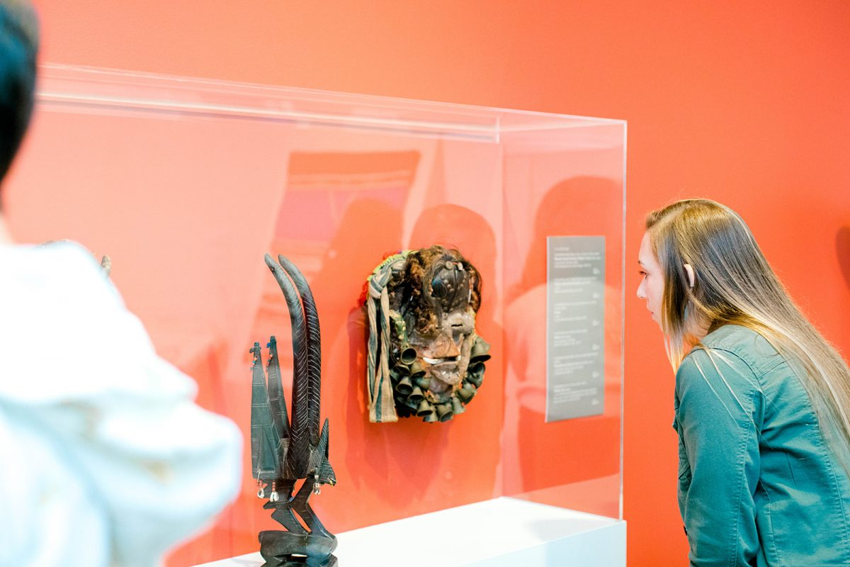 Person looks at an African mask in a glass case