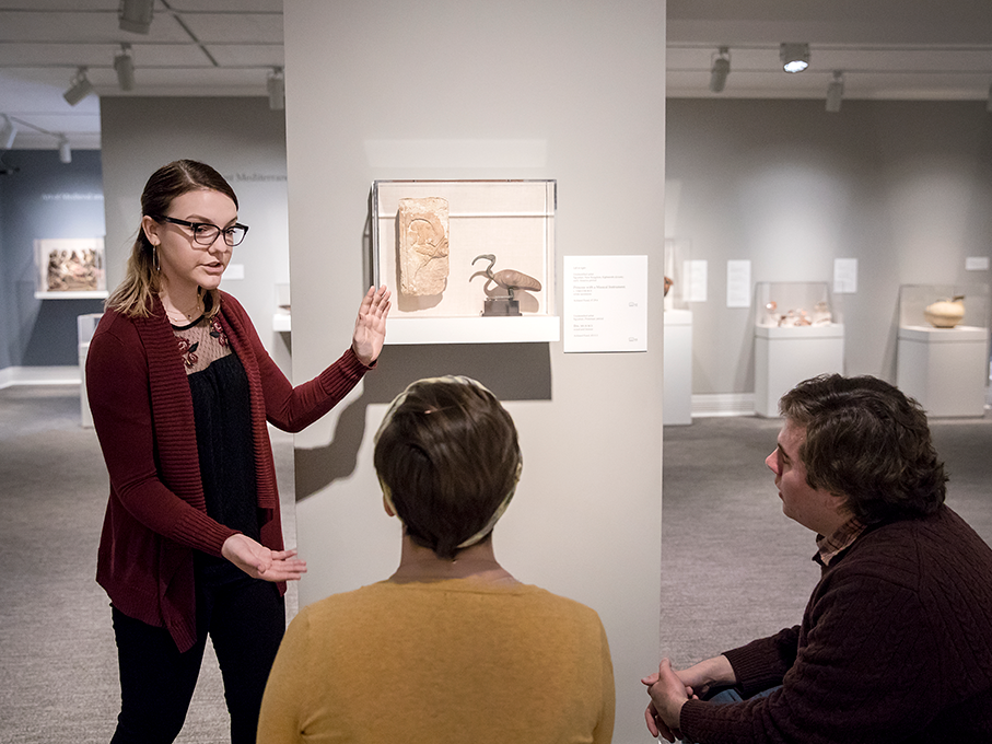 A student gives a presentation, pointing to an art object in a gallery