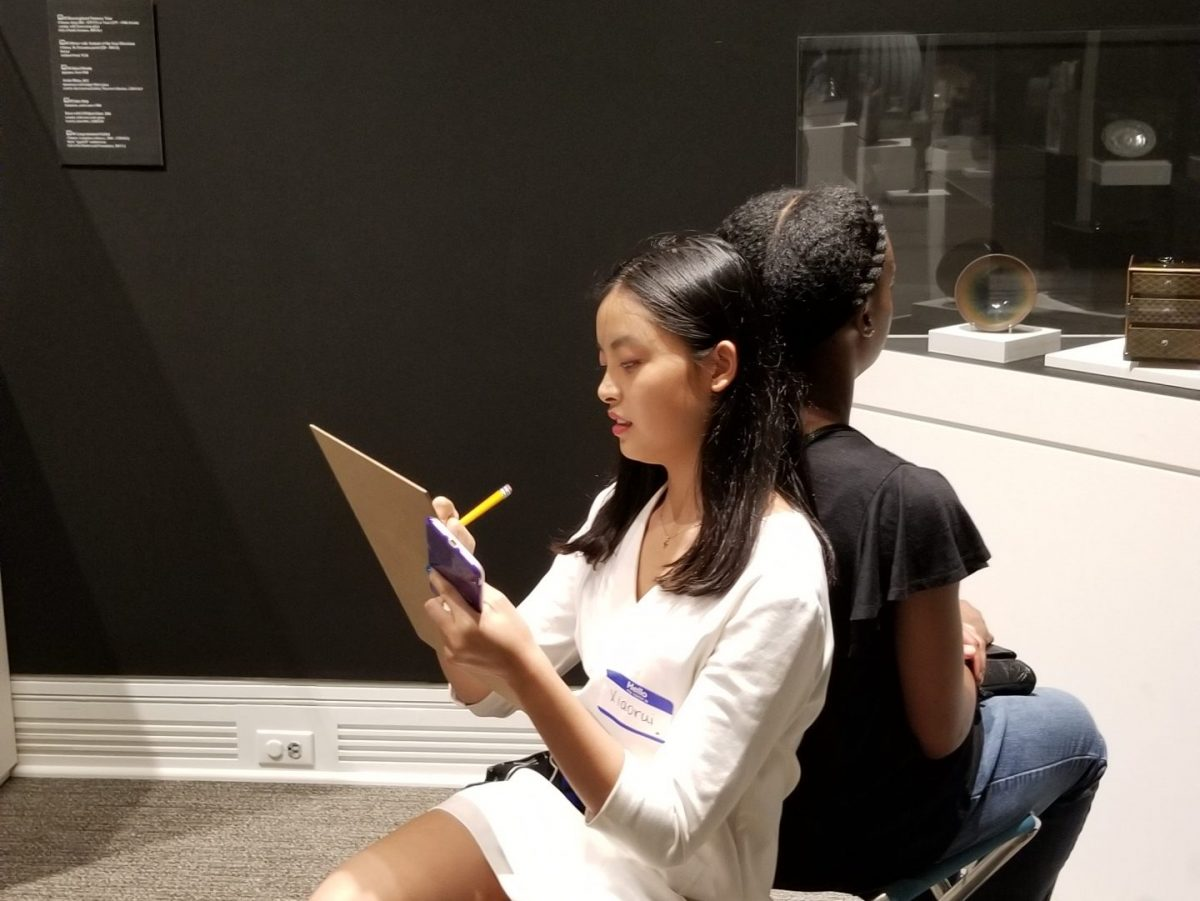 Students sit back to back in an art gallery while writing on clipboards