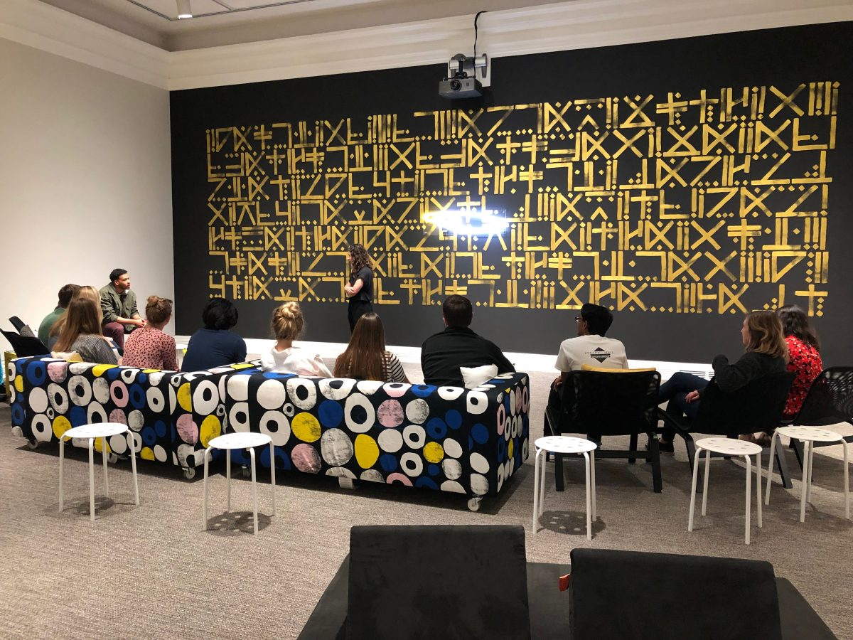 a group of people sits on couches in front of a black and gold mural
