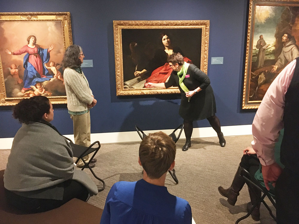 A person points to a painting of a man while a group sits in a semi circle watching