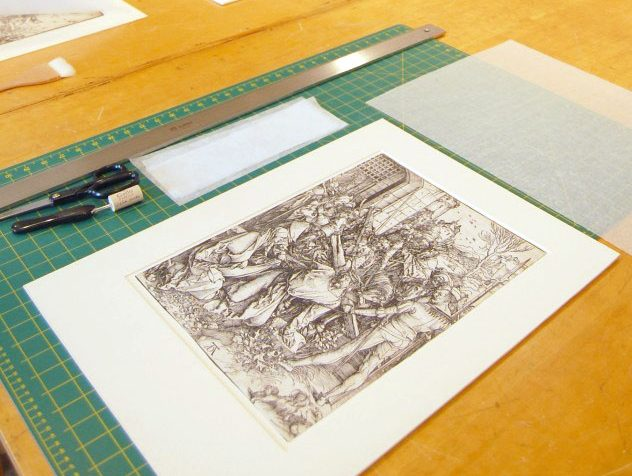 A drawing sits on a wood table in a conservation lab at the Ackland Art Museum