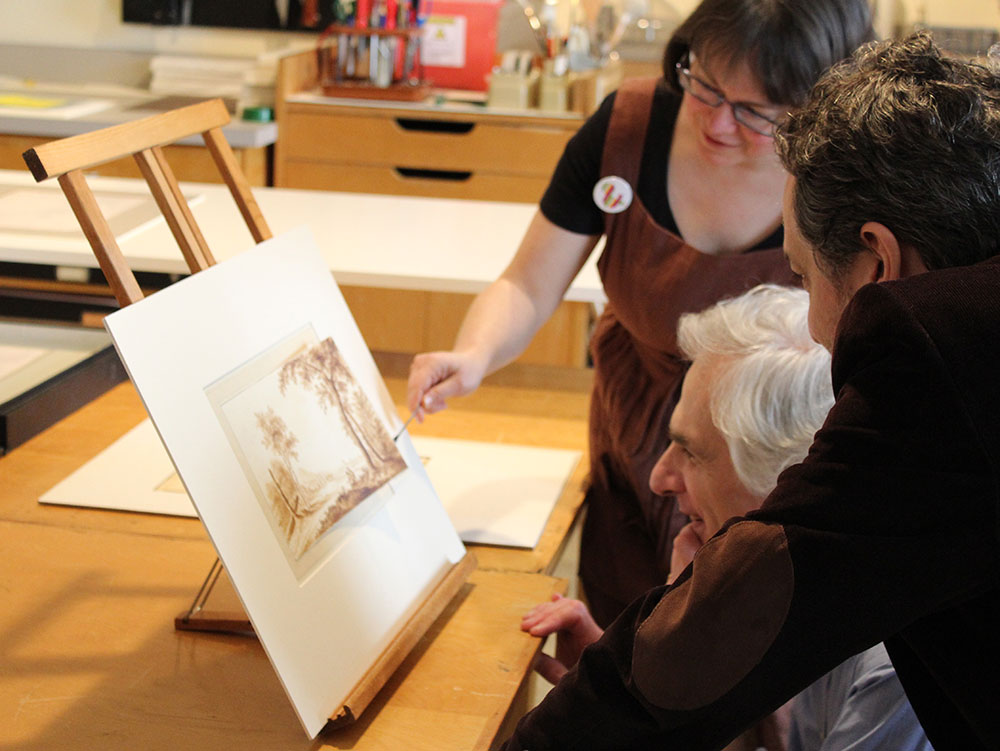 Three people look closely at a Rembrandt drawing in a conservation lab